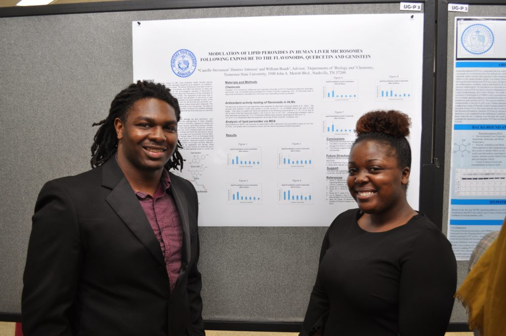 Biological Sciences and Chemistry Students standing in front of a poster
