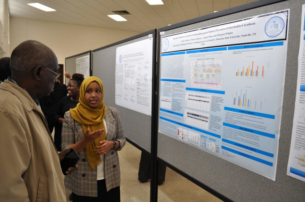 Chemistry Student presenting a poster